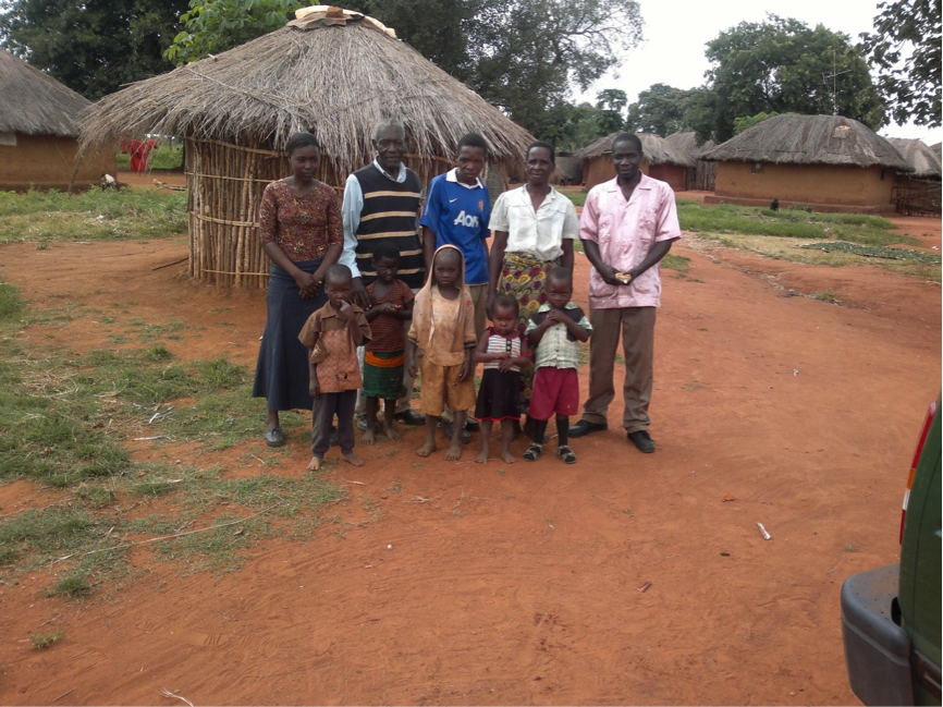 A woman and man stand with a group of children outside