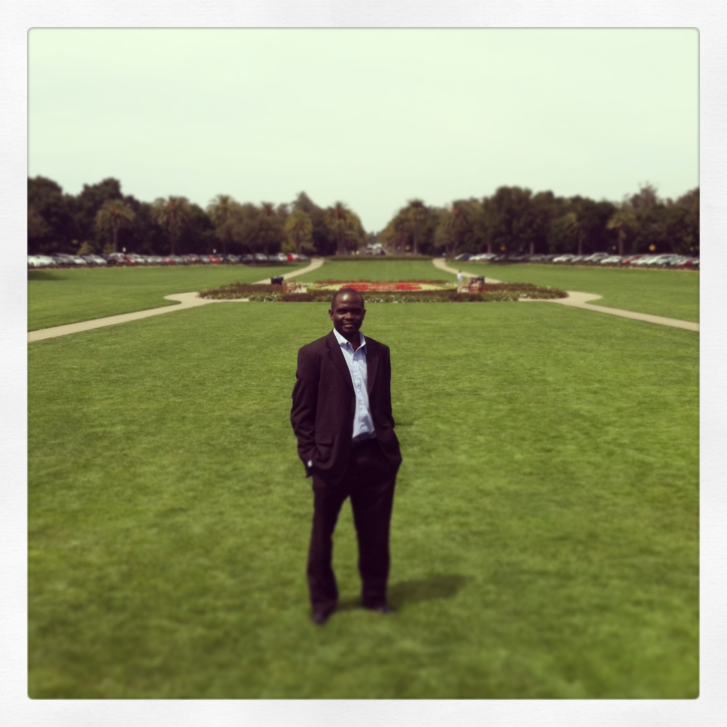 A man stands wearing a dark suit in a grassy field of a school campus