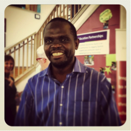 An African man smiling in a public building with a bulletin board behind him.