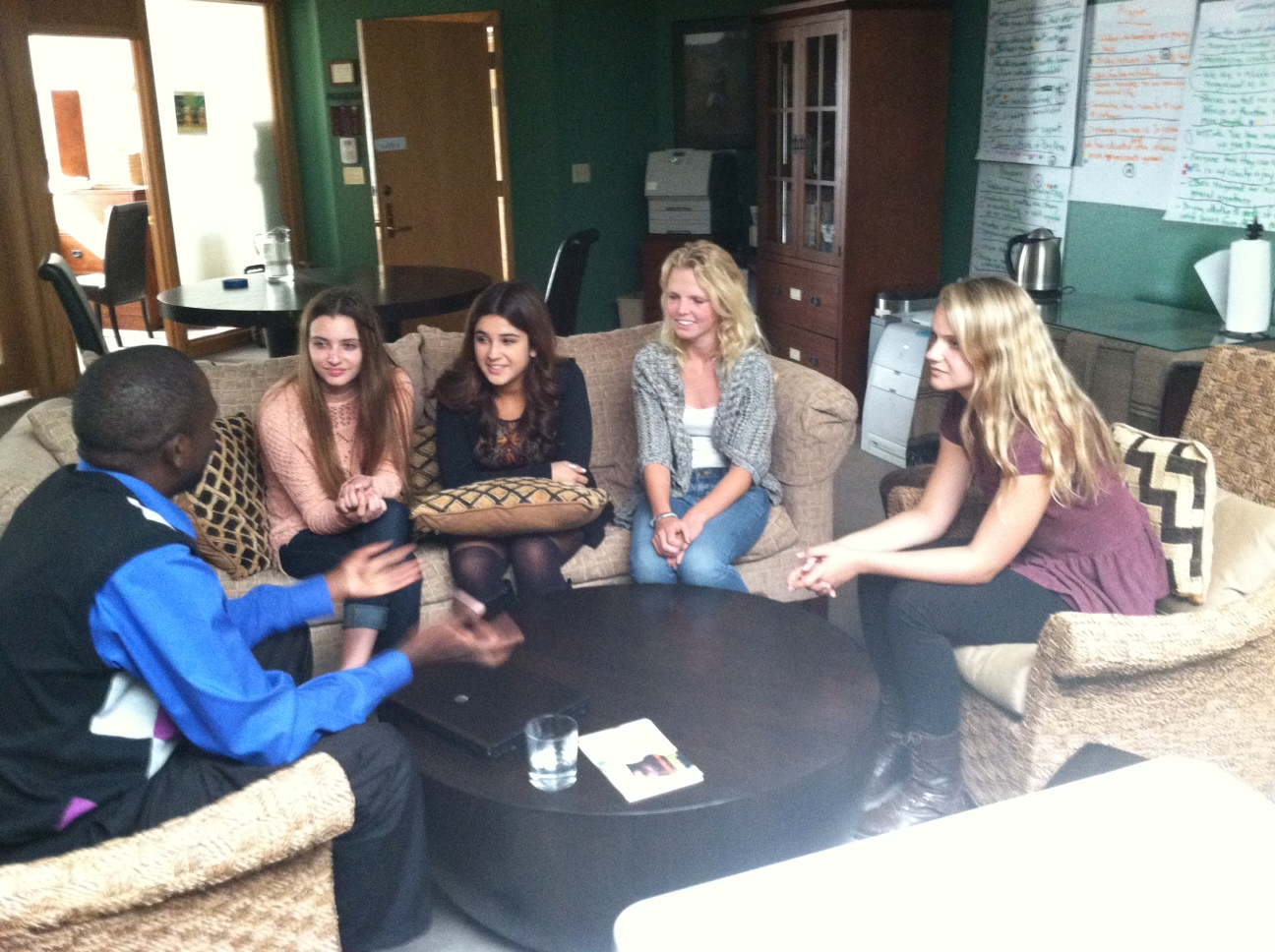A man talks with four teenagers around a table