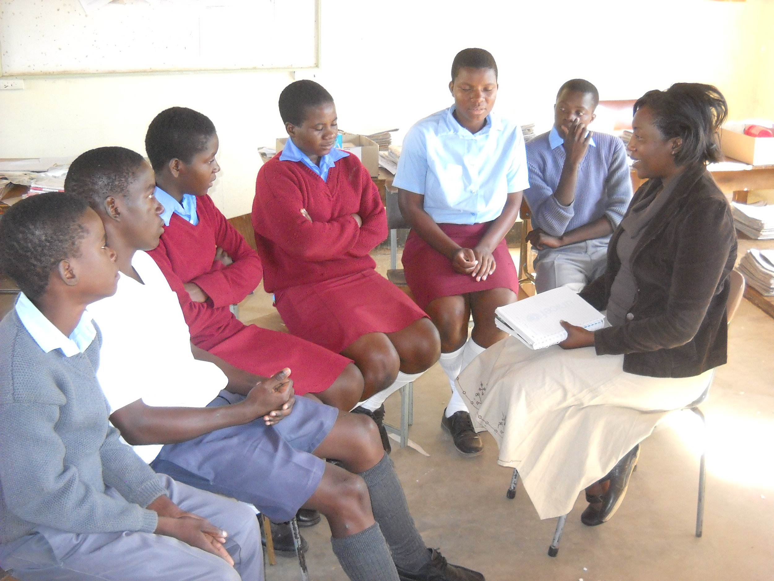 Six African children sit in a classroom wearing school uniforms and talking with an adult African woman