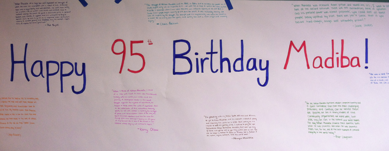a paper that says happy 95th birthday with writing all around it displayed on a green wall