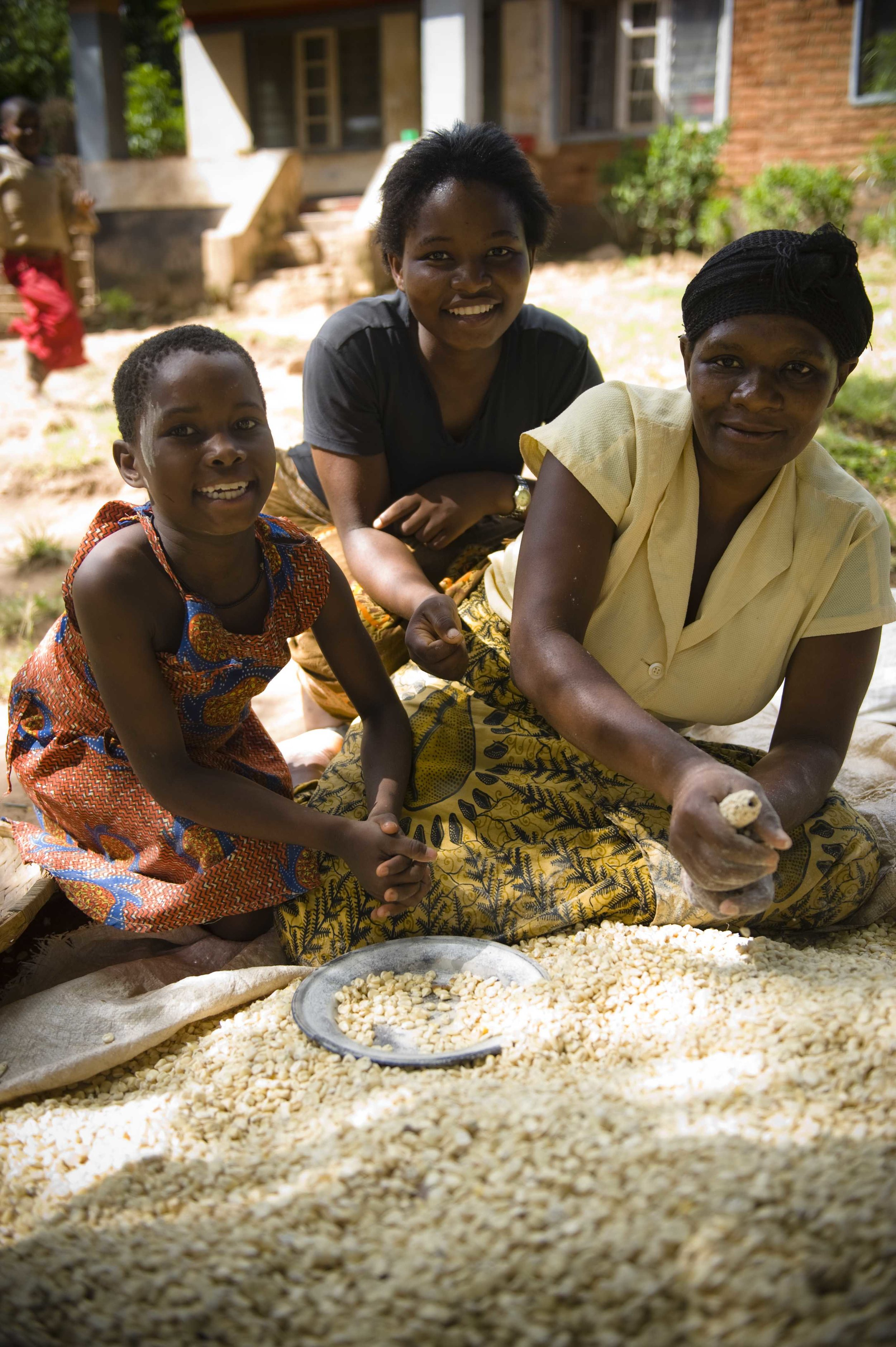 An African woman, a teenager and a child smile above a large pile of dry maize