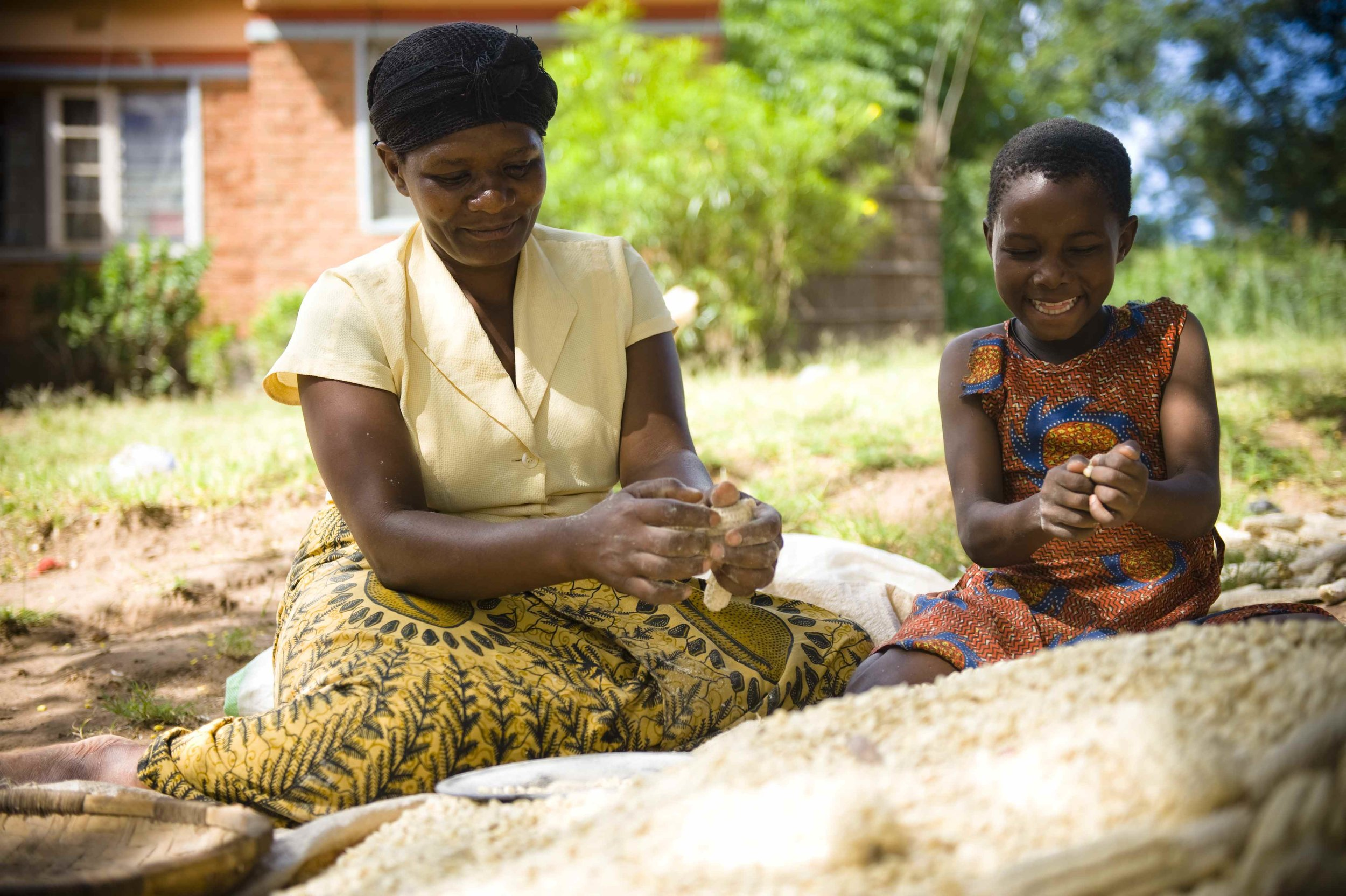 An older African woman and a young girl sit outside preparing maize