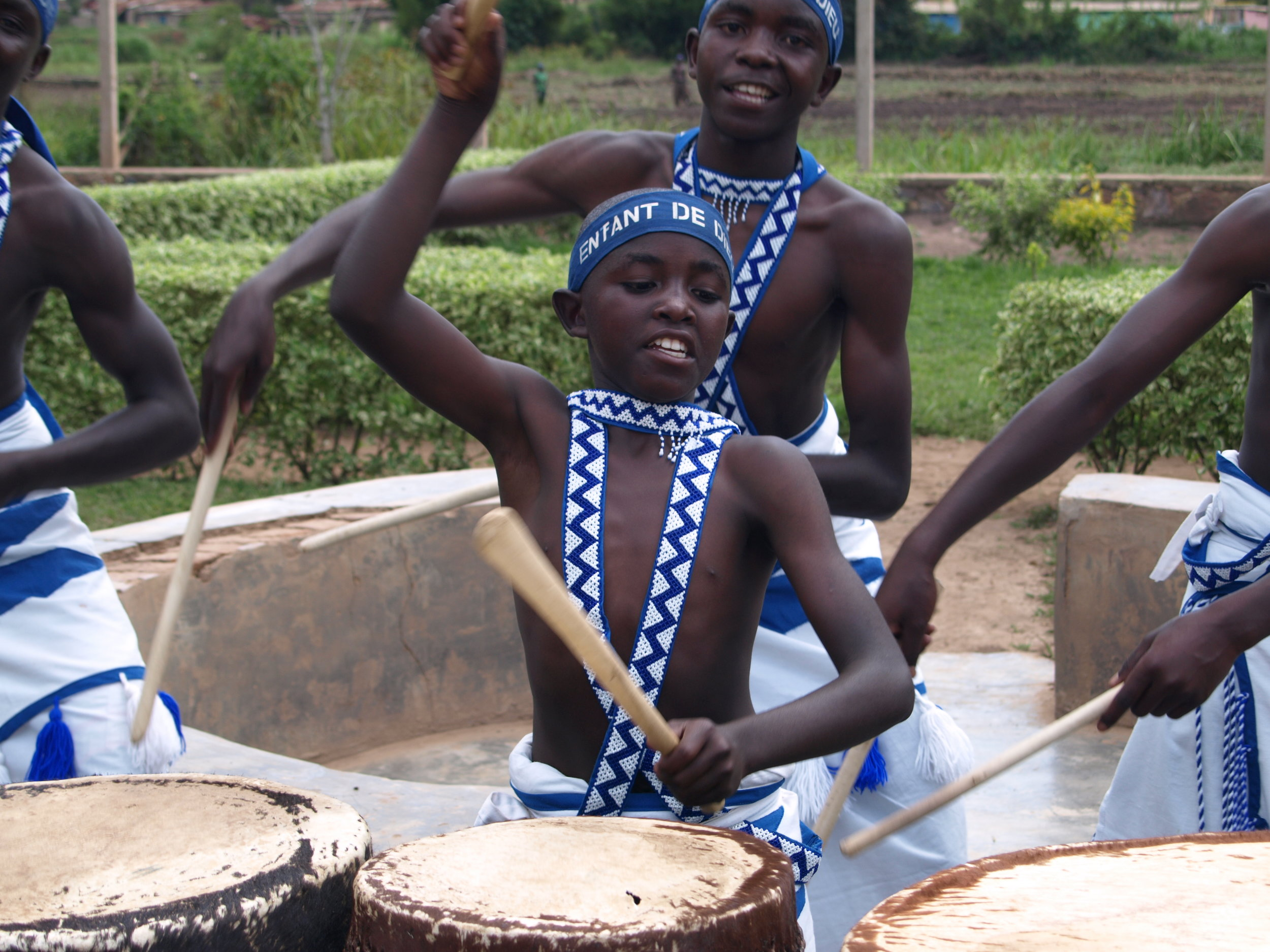 Children drumming in traditional blue and white dress playing drums