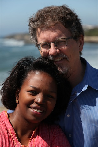 An African woman and American man stand leaning into each other on a beach