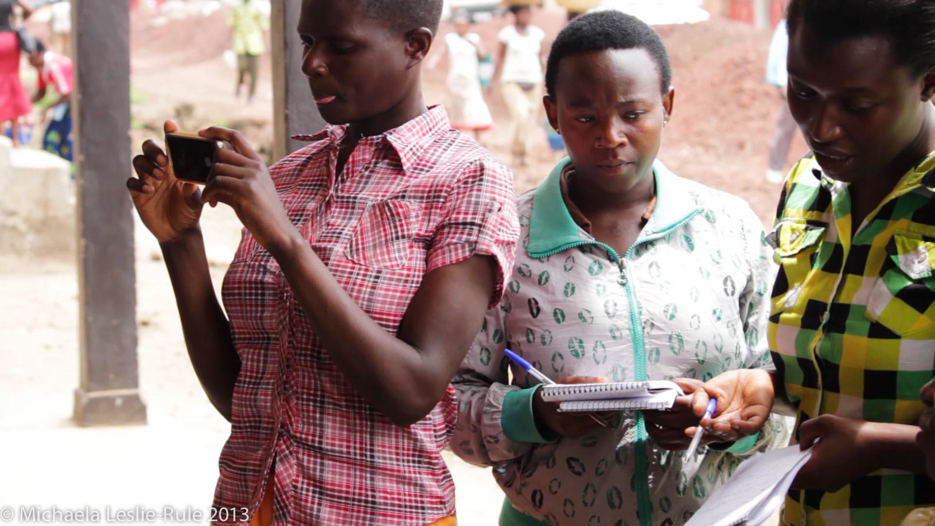 Three African girls group together. One is looking at her iPhone and two are holding notepads and pens.