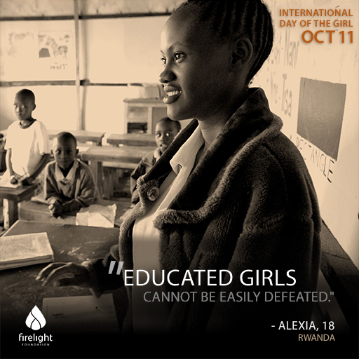 An African girl stands in a classroom smiling as other students watch her.