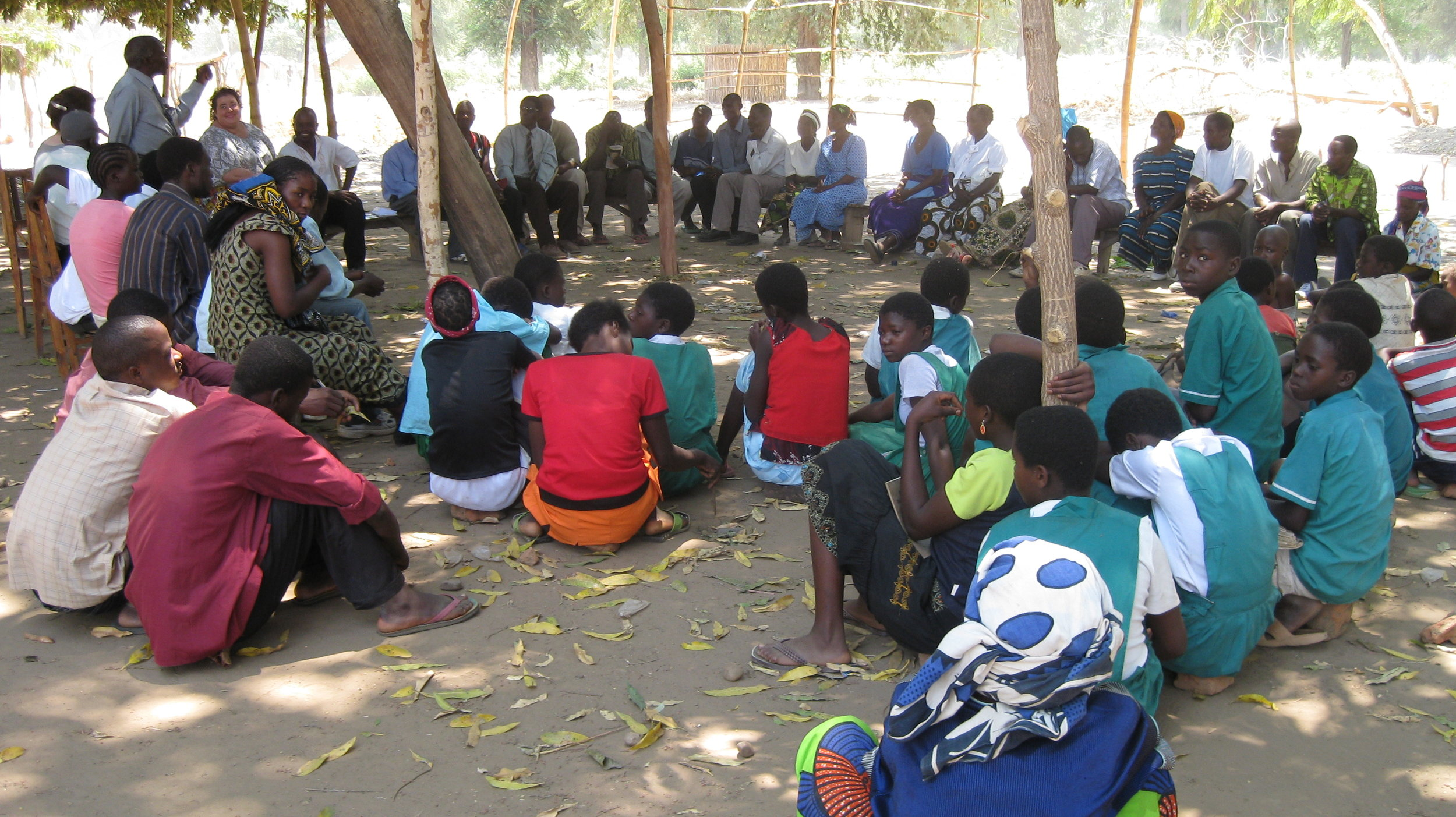 A group of African men, women and children gather outside in a shaded area under a tree.