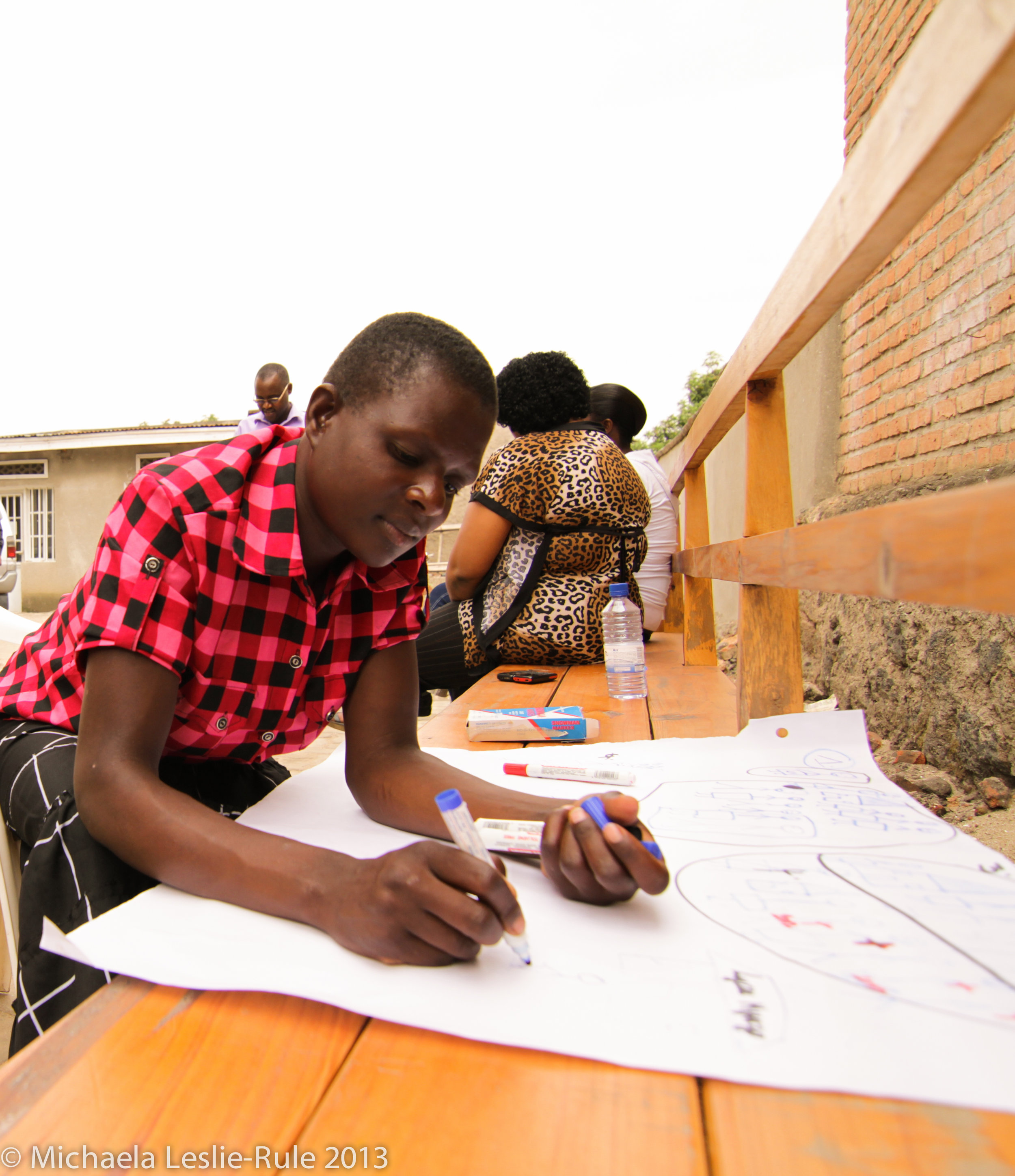 An African girl wearing a red and black checkered shirt writes on a large sheet of paper