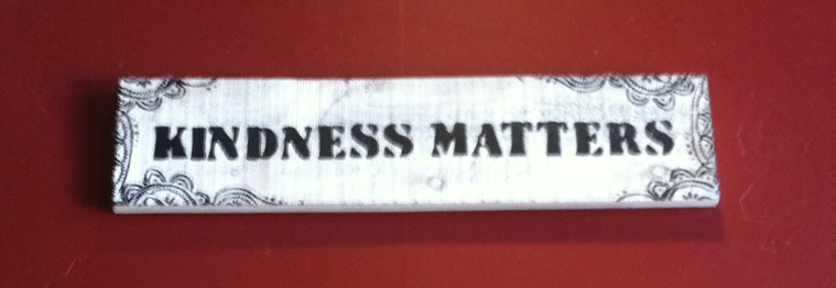 black lettered sign that reads Kindness Matters against a red wall