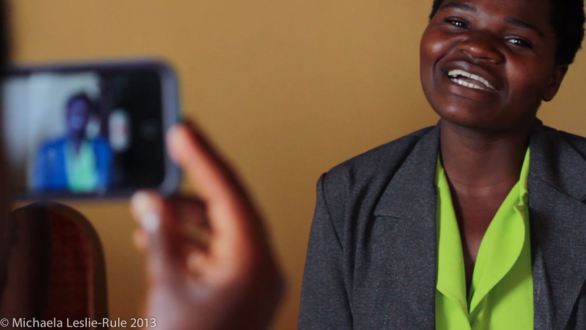 An African woman smiles as we see her and her image being recorded on an Apple iPhone