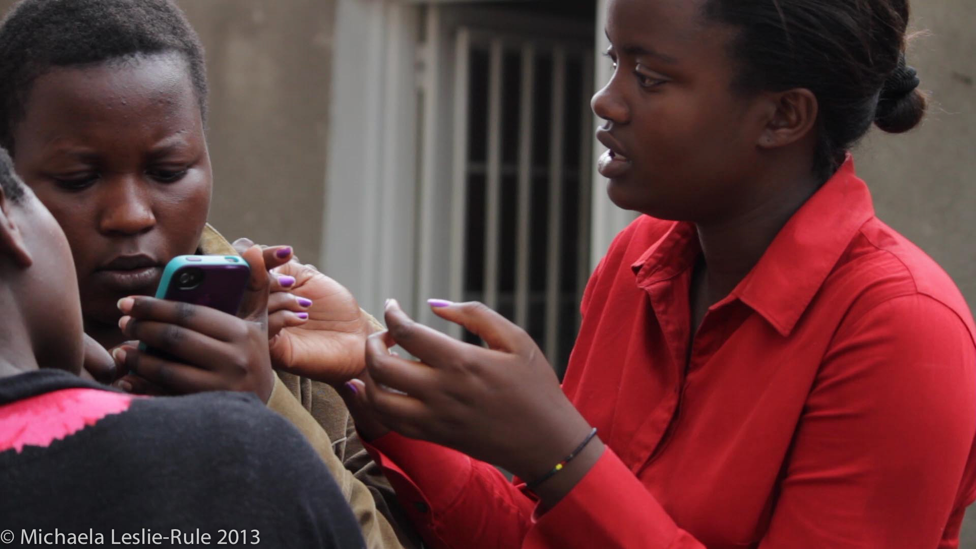 A woman talks to African girls, one is holding an iPhone