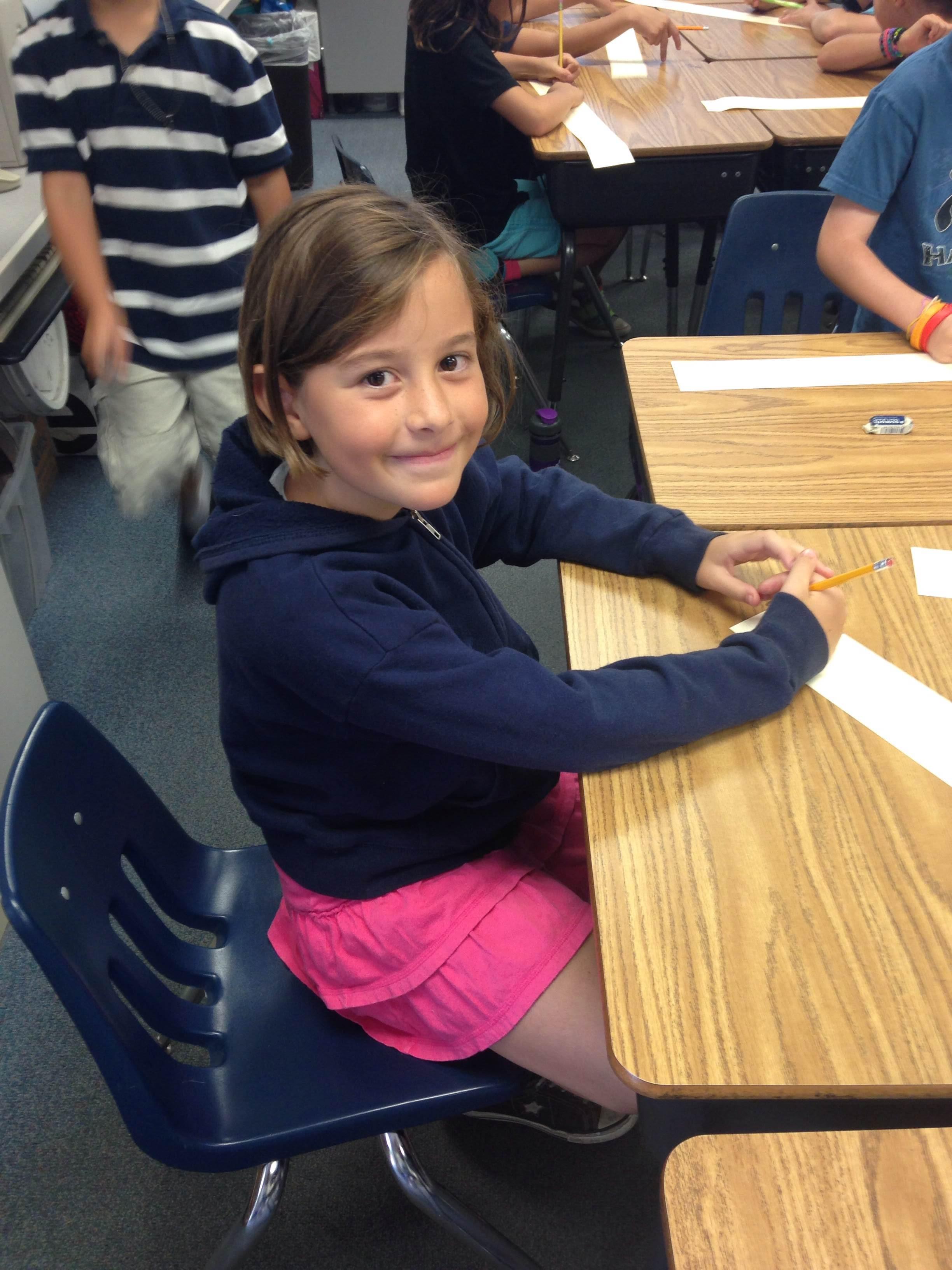 a third grade girl sits at a desk smiling at the camera