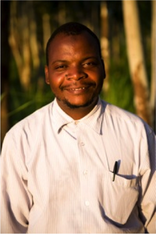 An African man smiles while standing outdoors