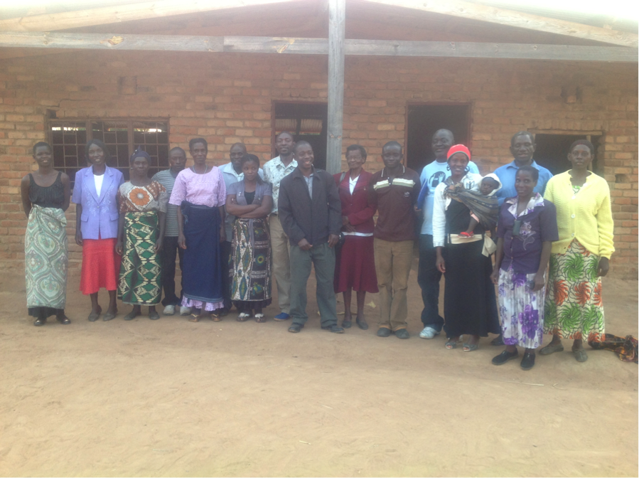 A group of African men and women stand in front of the Enukweni office