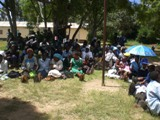 A large group of African children sit outside waiting for government officials to arrive