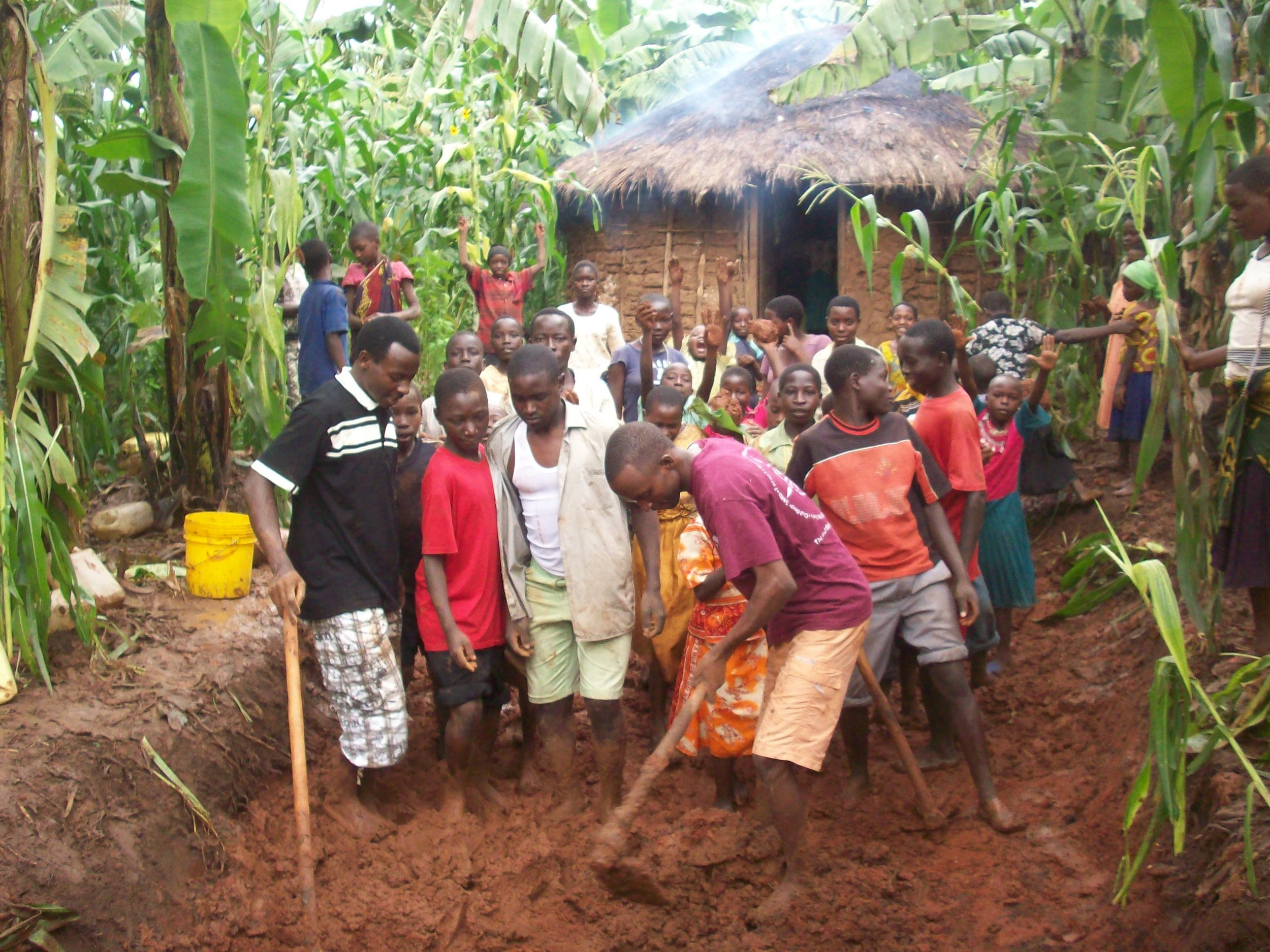 Kwa Wazee staff and children constructing a house for an older person in the community.