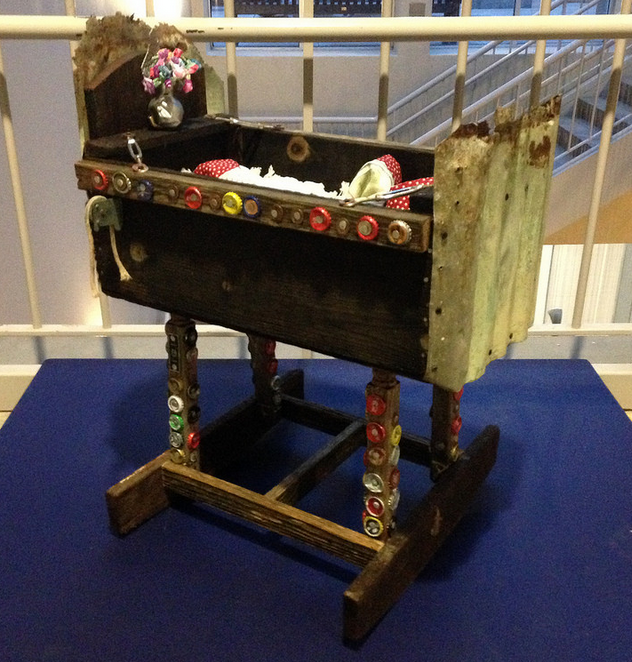 A wooden cradle with bottle caps and other items attached