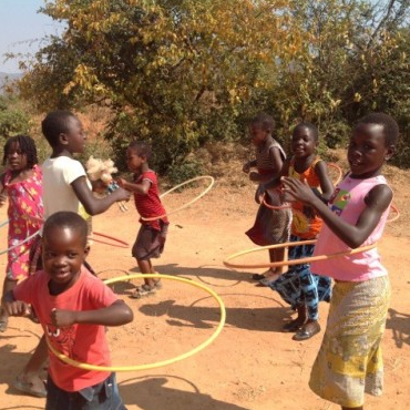 African children hoola-hooping outdoors in Malawi