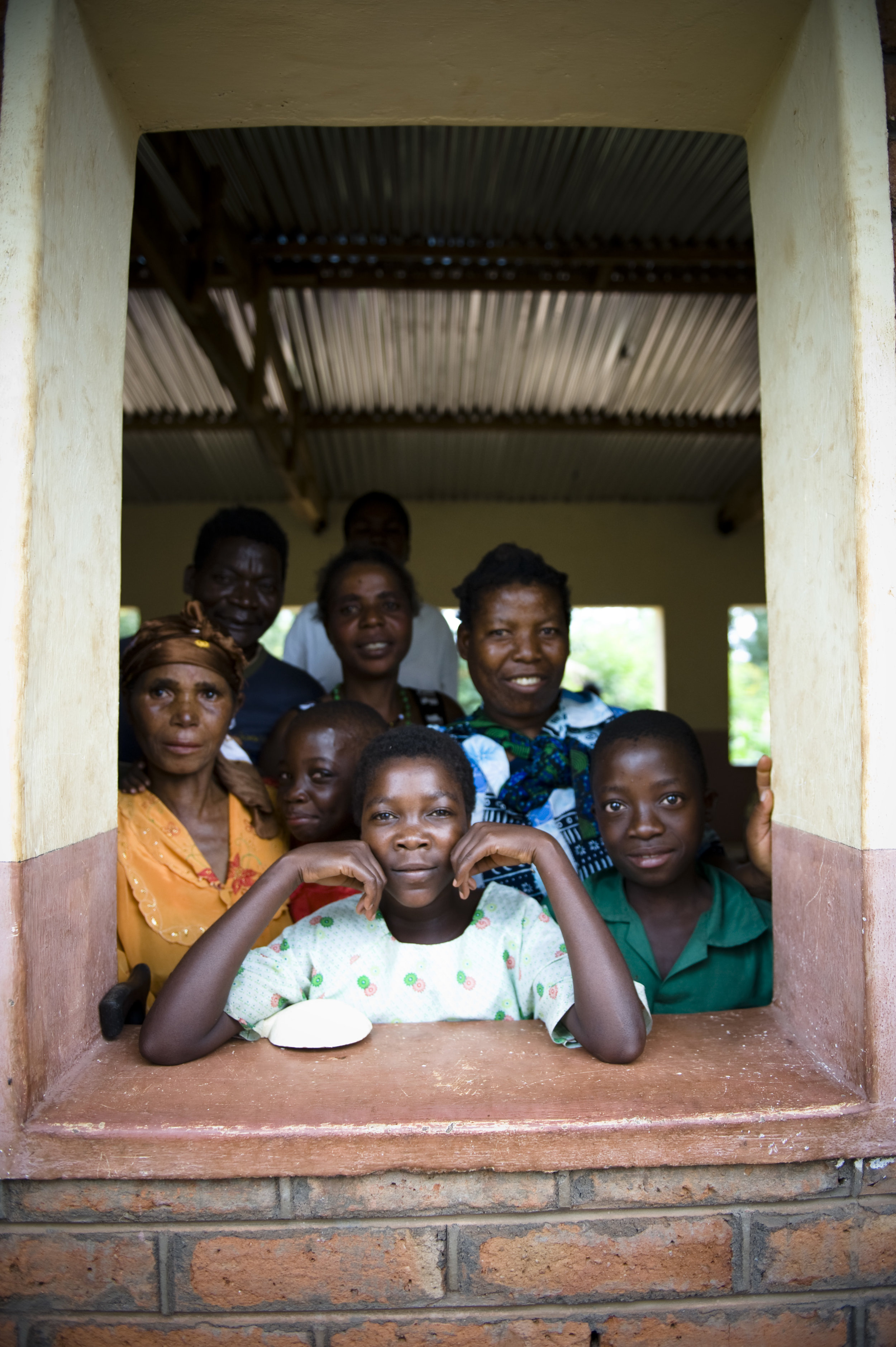 A group of African children and adults smile and look out a window