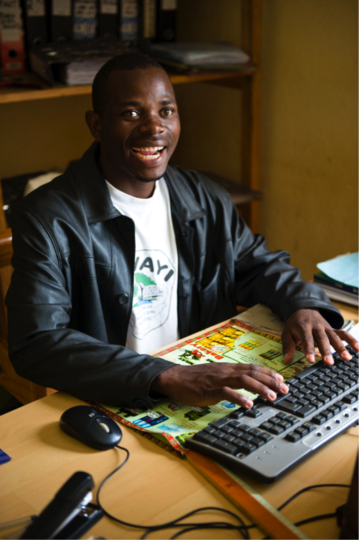 An African man smiles while typing on a computer keyboard