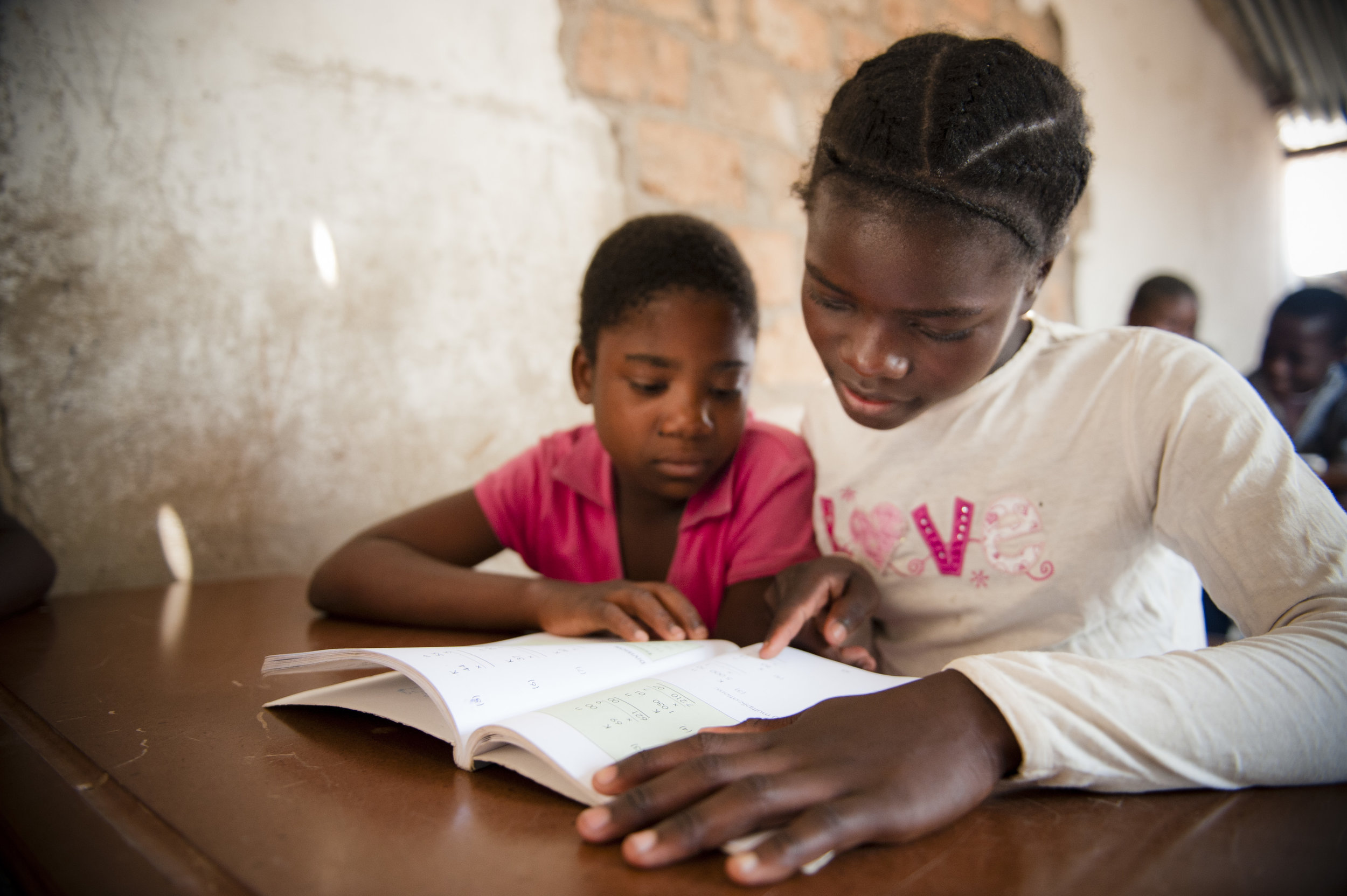 an older African girl looks at a text book with a younger African girl