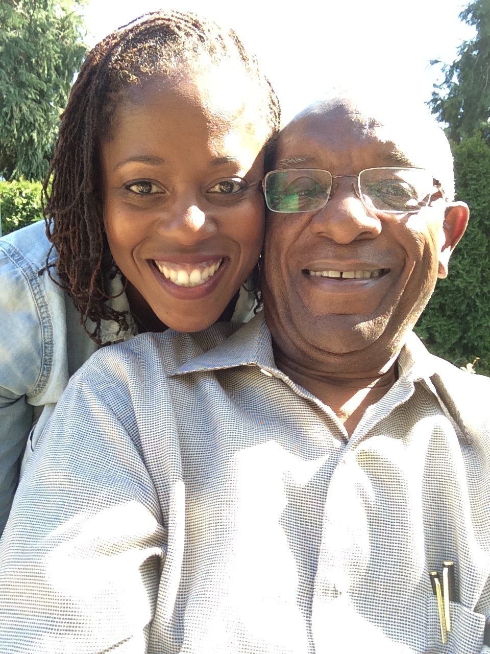 An African American daughter and father smiling.