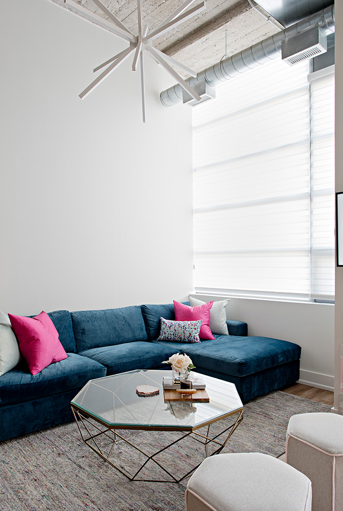 Velvet teal sectional with pink accent pillows and glass and brass coffee table in this urban loft modern but feminine remodel.