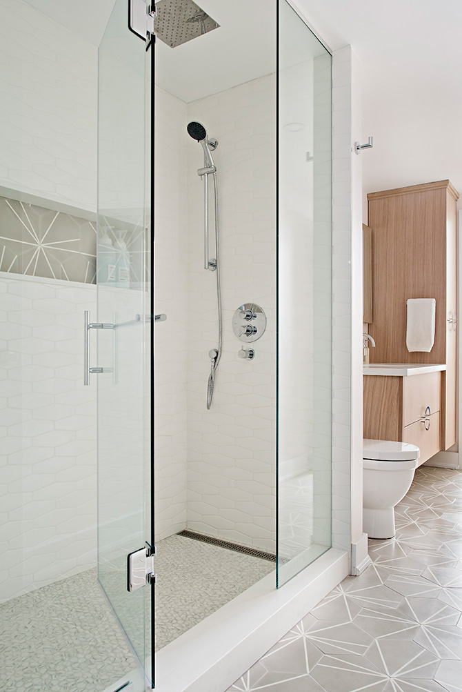 White shower wall tiles in geometric shape with chrome rain shower head and glass panel hinged shower door. Grey and white geometric cement bathroom floor tiles.
