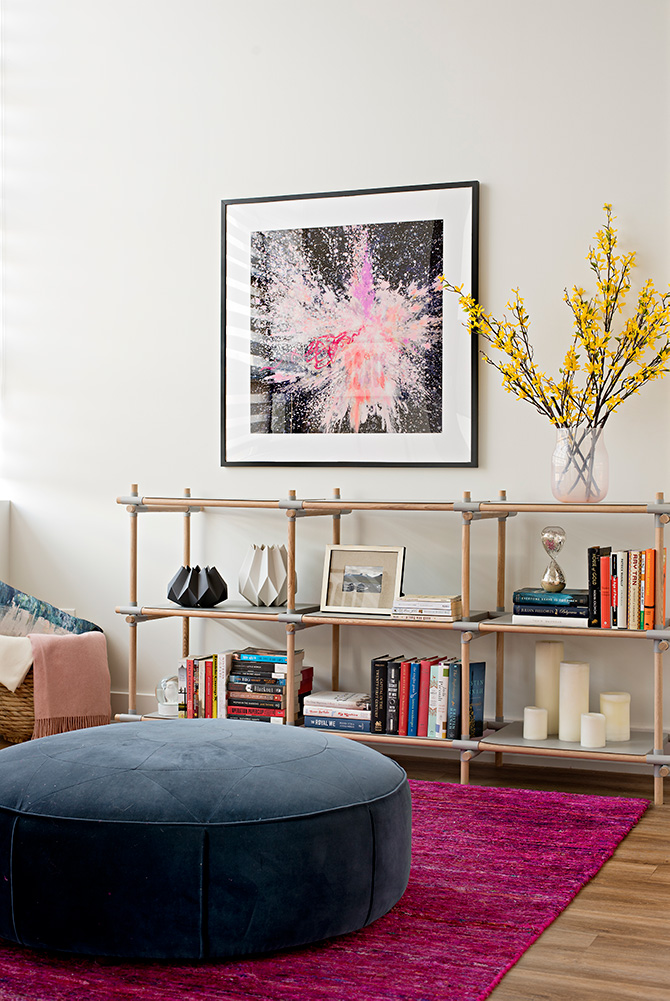 Fuchsia area rug and open book shelves with vibrant art in this urban loft design.