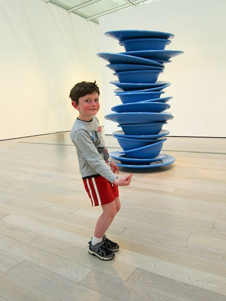Grandson holding up plates at Thierman Exhibit, LACMA
