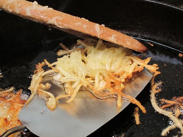 Turning over potato latkes