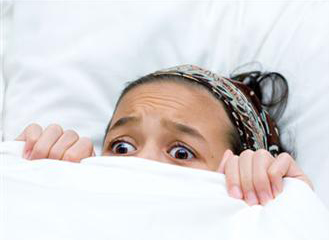 Woman in fear under blankets