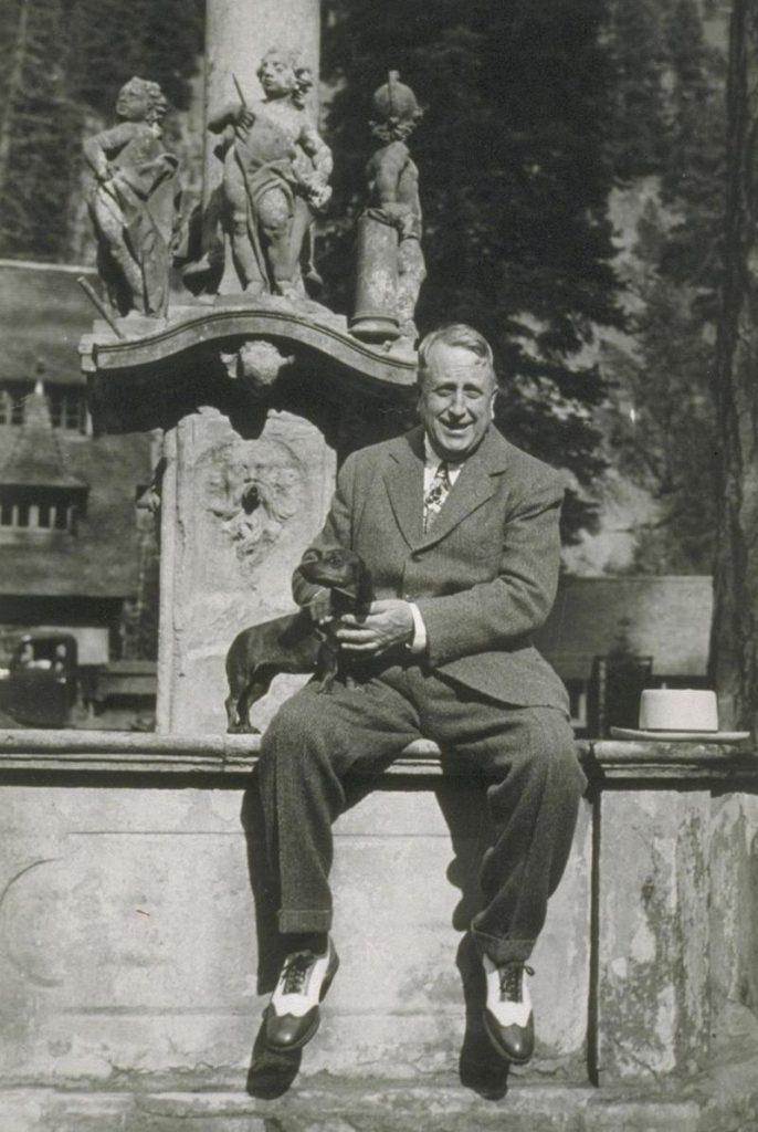 William Randolph Hearst sitting on a ledge.