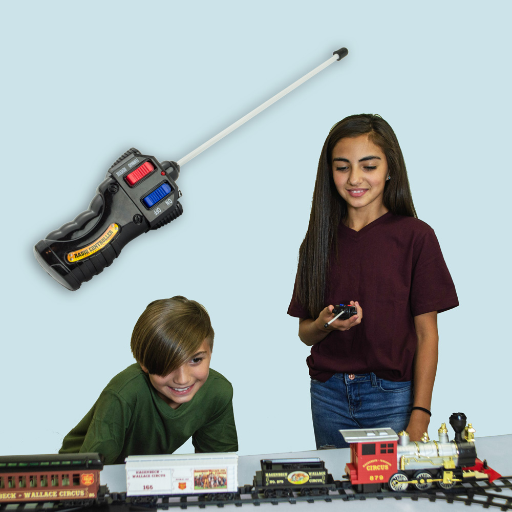 Children operating model train with remote control