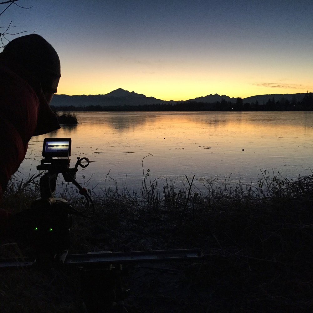 photographer taking picture of lake at sunset