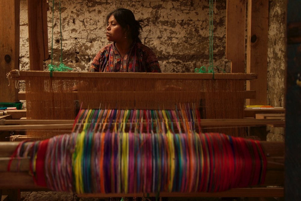 woman weaving colorful textiles