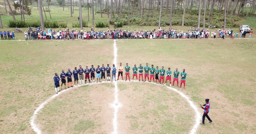 soccer teams standing in center of field
