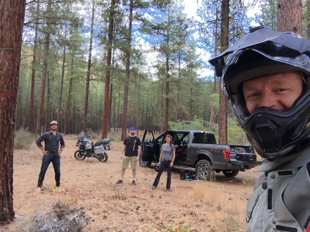 man with motorcycle helment in woods with three men and truck in background