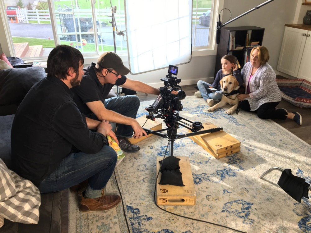 two photographers filming mother, daughter, and golden retriever in house
