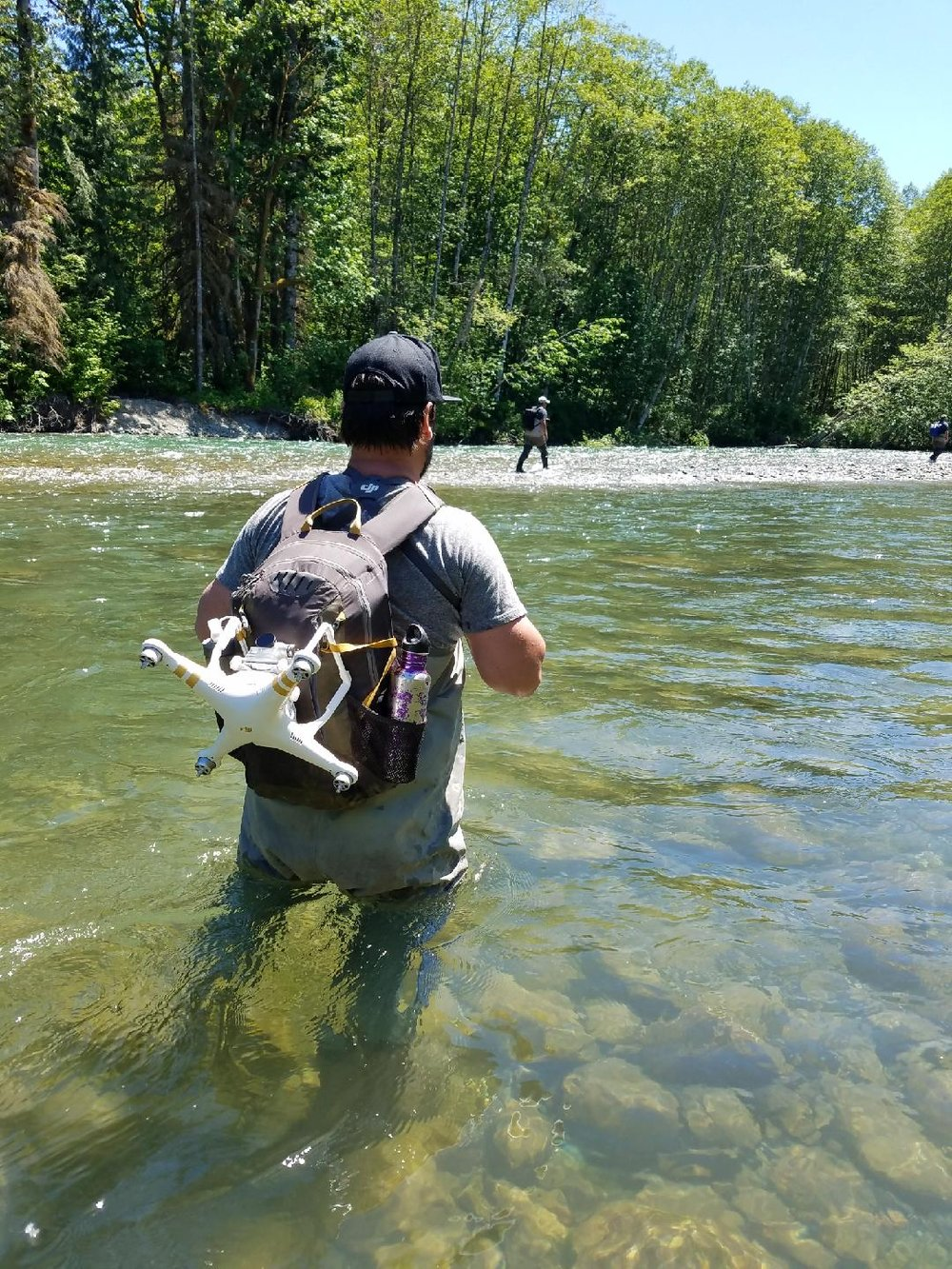 man wading through slow river with backpack and baseball cap