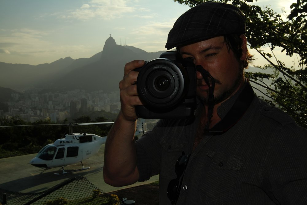 photographer with digital camera with helicopter and mountain in background