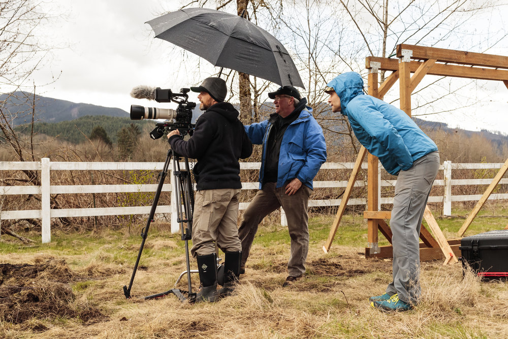 three men using video camera outdoors by barnyard fence