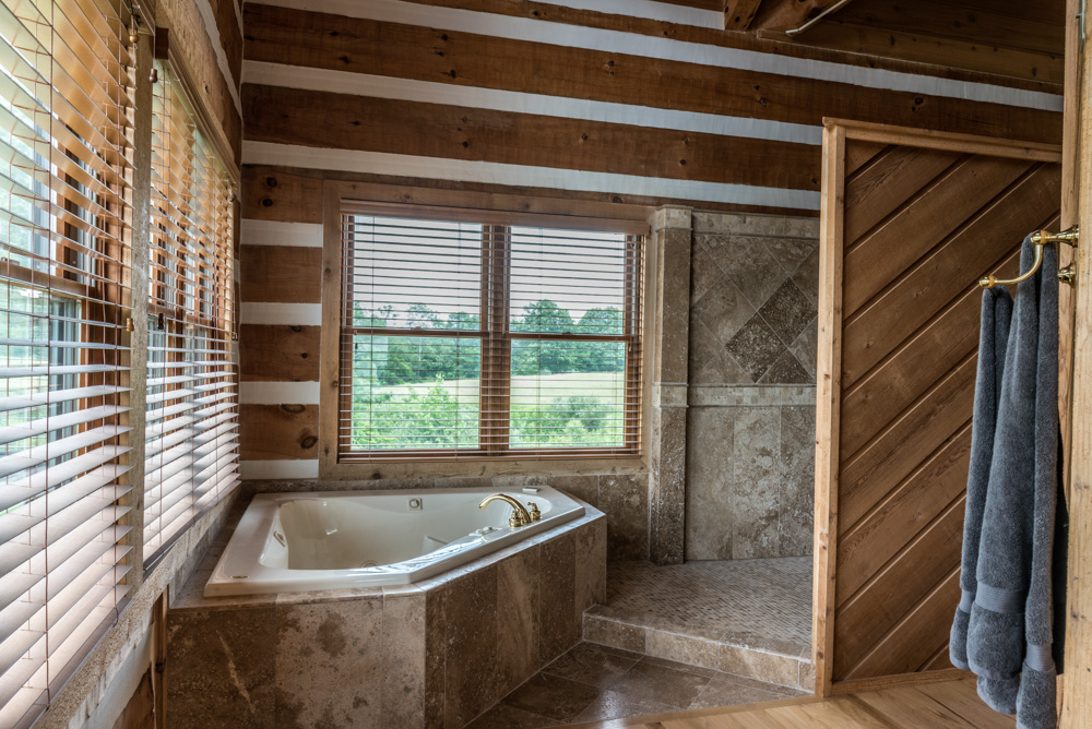 The master bathroom includes both a corner Jacuzzi with windows overlooking our fields on both sides and a spacious full tiled double shower.