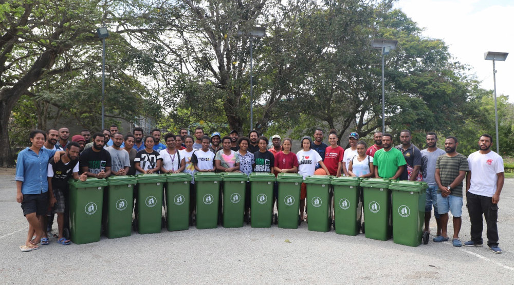 UPNG SMHS Students who participated in the clean-a-thon standing with the wheelie bins which will be placed in dormitories on campus.