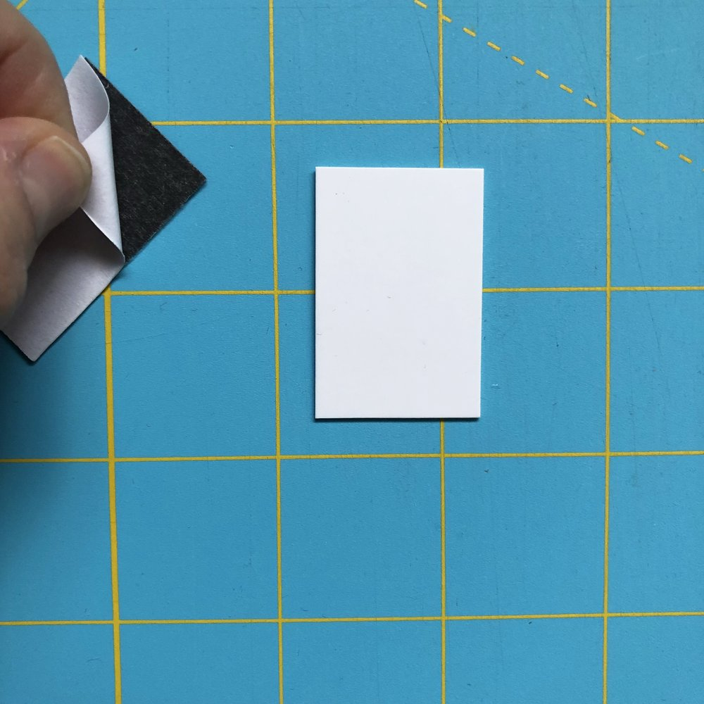 Peel off the paper backing and stick to the back of your swatch card. This material is very easy to cut so any magnetic sheet that is visible from the front you can just cut away using scissors.