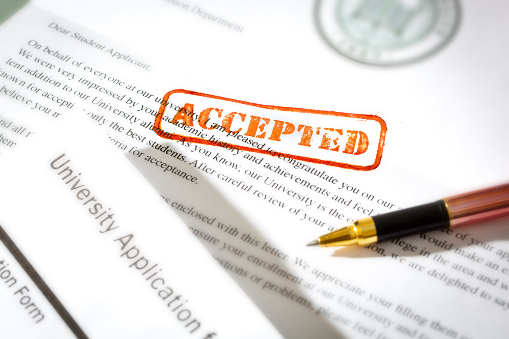 "Prospective students and incoming students apply for college and applications are stamped with the word ""ACCEPTED"""