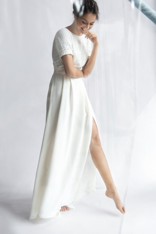Nathalie - Minimalistische boho chic – ivoorkleurige jurk met het accent op de taille – bovenstuk in twee stoffen: crêpezijde, daarboven geometrische kant; door de strakke, open lijn van de hals en de rug wordt de aandacht naar de rug getrokken– onderstuk uit gedrapeerde zijde, met een subtiel kort uitlopende sleep die in vloeiende lijnen rond de benen valt.