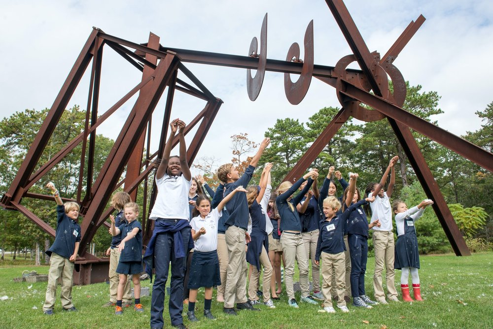 Elementary students disperse milkweed seeds as part of their study of the monarch butterfly system. Sculpture by Mark DiSuvero in background.